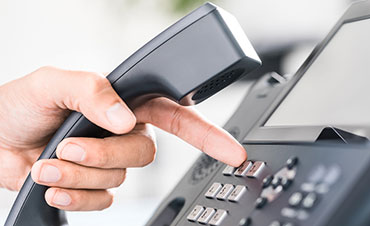 person dialing a business phone